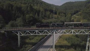 Locomotora de vapor en el puente - vista de drone en 4k video