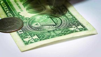 quatre pièces et billet d'un dollar sur une surface blanche