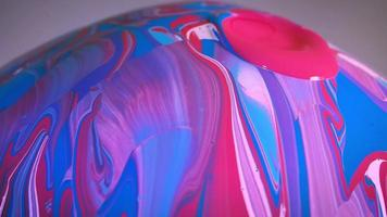 close-up de tinta azul rosa e branca na esfera de vidro