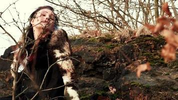 Hermosa mujer vikinga sentada sobre una roca en otoño paisaje natural video
