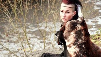 Hermosa mujer vikinga sentada sobre una roca en otoño paisaje natural