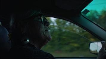Cerca de anciana conduciendo y hablando con un pasajero