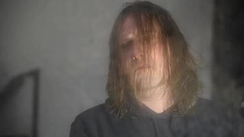 homem deprimido e zangado está sentado em frente a seu reflexo em uma velha casa abandonada video