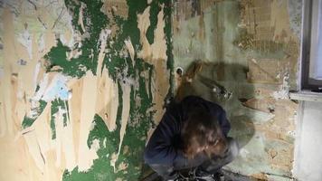 homem deprimido e louco bate contra a parede de uma casa abandonada video