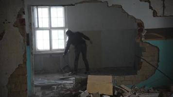 Hombre deprimido y loco lanza una silla a través de una habitación en una vieja casa abandonada