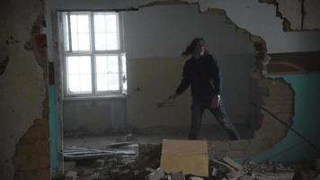 Deprimido y loco golpea una pared en una vieja casa abandonada