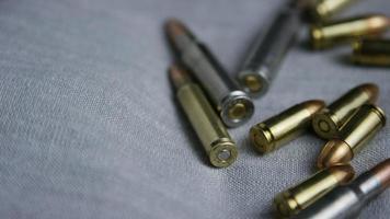 Disparo giratorio cinematográfico de balas sobre una superficie de tela - balas 096