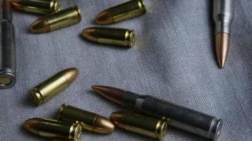 Disparo giratorio cinematográfico de balas sobre una superficie de tela - balas 091