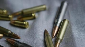 Disparo giratorio cinematográfico de balas sobre una superficie de tela - balas 097