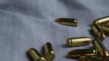Disparo giratorio cinematográfico de balas sobre una superficie de tela - balas 085