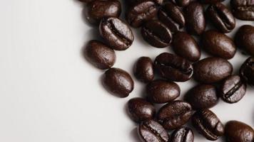 colpo rotante di deliziosi chicchi di caffè tostati su una superficie bianca - chicchi di caffè 032