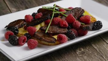 tomada rotativa de um delicioso prato de bacon de pato defumado com abacaxi grelhado, framboesas, amoras e mel - comida 099 video