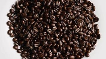 Rotating shot of delicious, roasted coffee beans on a white surface - COFFEE BEANS 054