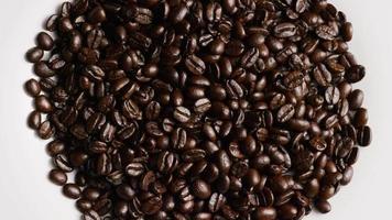 rotierender Schuss von köstlichen, gerösteten Kaffeebohnen auf einer weißen Oberfläche - Kaffeebohnen 054