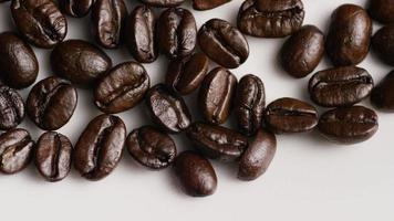 colpo rotante di deliziosi chicchi di caffè tostati su una superficie bianca - chicchi di caffè 033