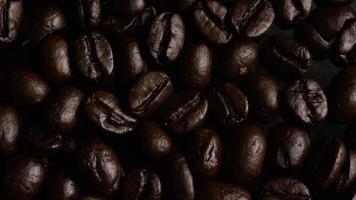 colpo rotante di deliziosi chicchi di caffè tostati su una superficie bianca - chicchi di caffè 007