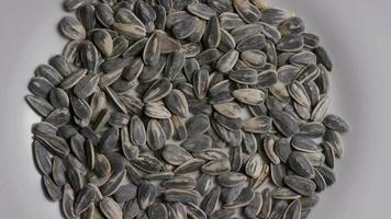 Cinematic, rotating shot of sunflower seeds on a white surface - SUNFLOWER SEEDS 001