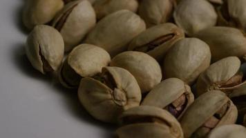 Cinematic, rotating shot of pistachios on a white surface - PISTACHIOS 016