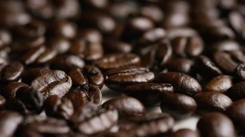 colpo rotante di deliziosi chicchi di caffè tostati su una superficie bianca - chicchi di caffè 053