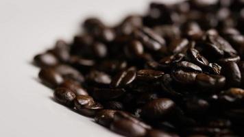 colpo rotante di deliziosi chicchi di caffè tostati su una superficie bianca - chicchi di caffè 078