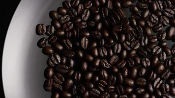 colpo rotante di deliziosi chicchi di caffè tostati su una superficie bianca - chicchi di caffè 004