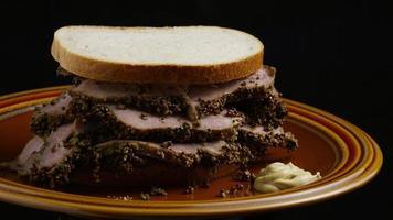 dose rotativa de delicioso sanduíche de pastrami premium ao lado de um bocado de mostarda dijon - alimento 032