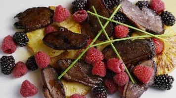 tiro giratório de um delicioso prato de bacon de pato defumado com abacaxi grelhado, framboesas, amoras e mel - comida 092 video