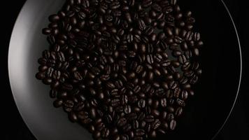 Rotating shot of delicious, roasted coffee beans on a white surface - COFFEE BEANS 001