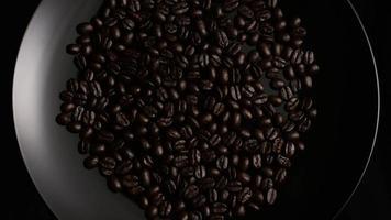 rotierender Schuss von köstlichen, gerösteten Kaffeebohnen auf einer weißen Oberfläche - Kaffeebohnen 001