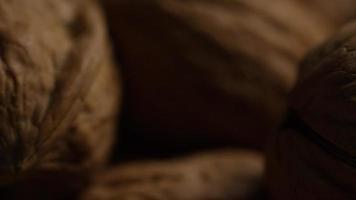 filmische, rotierende Aufnahme von Walnüssen in ihren Schalen auf einer weißen Oberfläche - Walnüsse 094