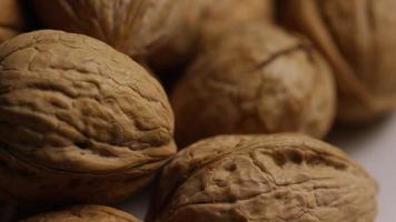 filmische, roterende opname van walnoten in hun schelp op een wit oppervlak - walnoten 076