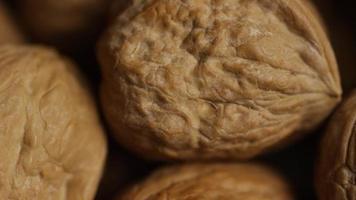 filmische, roterende opname van walnoten in hun schelpen op een wit oppervlak - walnoten 066