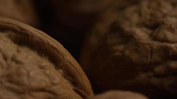 filmische, rotierende Aufnahme von Walnüssen in ihren Schalen auf einer weißen Oberfläche - Walnüsse 020