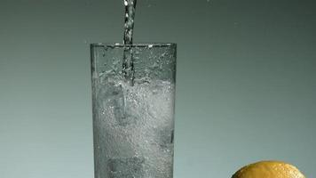 líquido transparente carbonatado que se vierte y salpica en cámara ultra lenta (1,500 fps) en un vaso lleno de hielo - líquido vertido 020