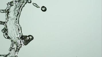 agua que se vierte y salpica en cámara ultra lenta (1,500 fps) sobre una superficie reflectante: el agua se vierte 135