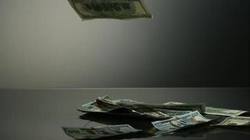 banconote da $ 100 americane che cadono su una superficie riflettente - fantasma di denaro 071