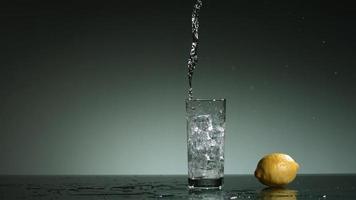 líquido transparente carbonatado que se vierte y salpica en cámara ultra lenta (1,500 fps) en un vaso lleno de hielo - líquido vertido 026