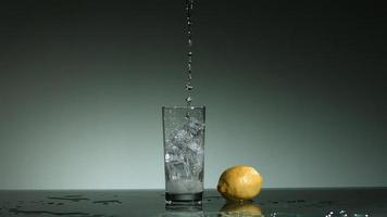 líquido transparente carbonatado que se vierte y salpica en cámara ultra lenta (1,500 fps) en un vaso lleno de hielo - líquido vertido 023