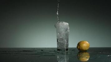 líquido transparente carbonatado que se vierte y salpica en cámara ultra lenta (1,500 fps) en un vaso lleno de hielo - líquido vertido 012