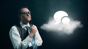 gracioso nerd o geek mirando a una nube voladora con un icono de burbuja de discurso giratorio