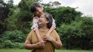 Cámara lenta de abuela feliz con nieta jugando en el parque