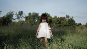 câmera lenta, menina caminhando na grama verde