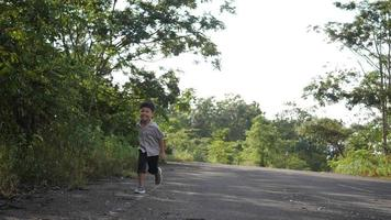feliz niño asiático corriendo en la calle