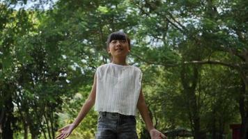 Niña asiática jugando al aire libre en cámara lenta, girando y sonriendo y levantando las manos en el aire