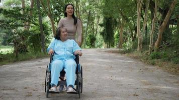 mulher mais velha com a filha empurrando cadeira de rodas pelo parque