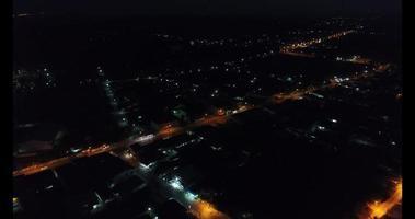 uma vista aérea sobrevoando uma cidade da Tailândia à noite