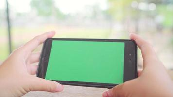 Young asian woman using black mobile phone device with green screen.
