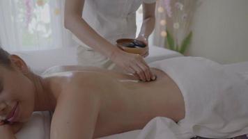 jovem fazendo massagem com pedras quentes no spa