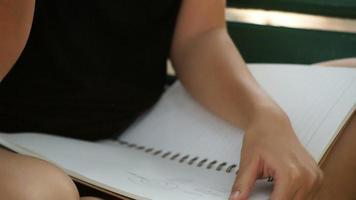hipster feliz jovem mulher asiática, escrevendo em seu diário no parque.