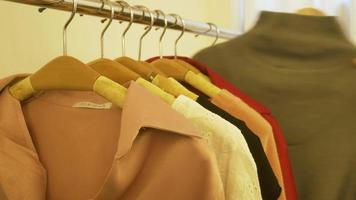 huis garderobe of kledingwinkel kleedkamer. Aziatische jonge vrouw die haar kleren van de manieruitrusting in kast thuis of opslag kiest.
